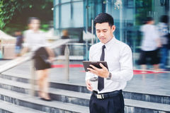 Affärsman som utomhus använder ett digitalt minnestavlakontor och suddigt P royaltyfri fotografi