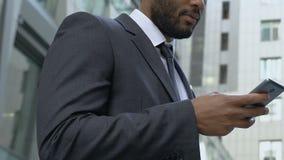 Affärsman som utomhus använder smartphonen, app för upptaget folk, påminnelse för bråklista stock video