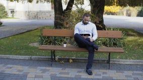 Affärsman som utomhus arbetar på minnestavlan på bänken 4K arkivfilmer