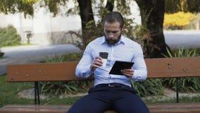 Affärsman som utomhus arbetar på minnestavlan på bänken 4K stock video