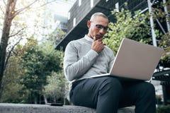 Affärsman som utomhus arbetar på sammanträde för bärbar datordator fotografering för bildbyråer