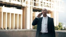 Affärsman som utomhus talar över den stående mobiltelefonen arkivfoto