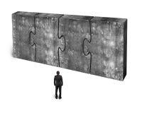 Affärsman som vänder mot fyra enorma betongpussel förbindelse tillsammans Arkivbild