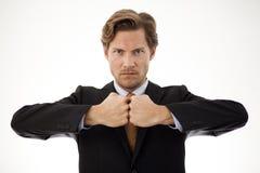 Affärsman som vänder mot hans nävar i ett tecken av styrka Arkivfoton