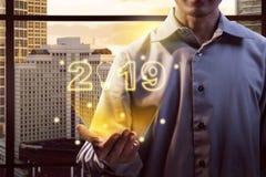 Affärsman som visar 2019 digitalt nummer från hans händer arkivfoton