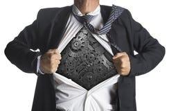 Affärsman som visar en superherodräkt under maskineri royaltyfri bild