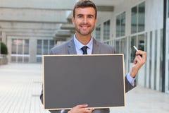 Affärsman som visar en svart tavla med utrymme för kopia Arkivfoton