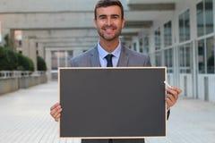 Affärsman som visar en svart tavla med utrymme för kopia Royaltyfri Fotografi