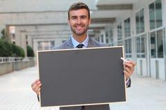 Affärsman som visar en svart tavla med utrymme för kopia Fotografering för Bildbyråer