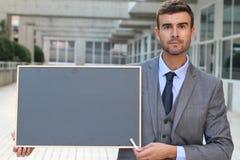 Affärsman som visar en svart tavla med utrymme för kopia Royaltyfria Bilder