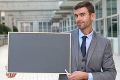 Affärsman som visar en svart tavla med utrymme för kopia Royaltyfria Foton