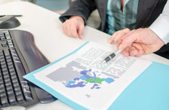 Affärsman som visar ett ekonomiskt dokument med en penna Royaltyfri Foto