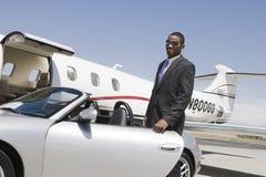 Affärsman Standing By Car på flygfältet Arkivbild