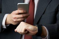 Affärsman Synchronizing Smart Watch med mobiltelefonen fotografering för bildbyråer