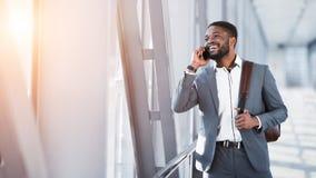 Affärsman Talking On Phone som går i flygplats royaltyfri fotografi
