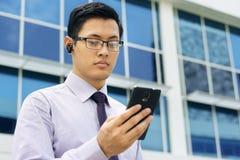 Affärsman Talking Video Call på mobil med den Bluetooth hörlurar med mikrofon Arkivfoton