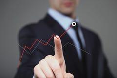 Affärsman Touching en graf som indikerar tillväxt Arkivfoton