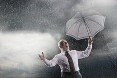 Affärsman With Umbrella Laughing i storm arkivfoto