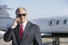 Affärsman Using Cell Phone med privata Jet In Background royaltyfria bilder