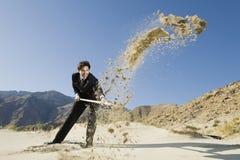 Affärsman Using en skyffel i öken Royaltyfri Bild