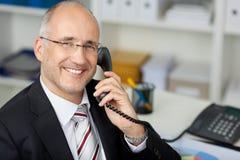 Affärsman Using Landline Phone på skrivbordet royaltyfri foto