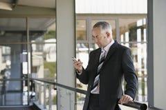 Affärsman Using Mobile Phone i regeringsställning Royaltyfria Bilder