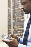 Affärsman Using PDA utanför byggnad royaltyfri fotografi