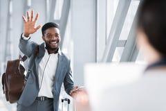 Affärsman Waving To Partner som väntar på honom i flygplats royaltyfria foton