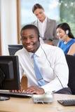 Affärsman Wearing Headset Working i upptaget kontor Fotografering för Bildbyråer