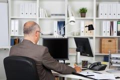Affärsman Working At Desk royaltyfria bilder