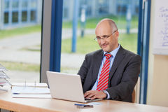 Affärsman Working On Laptop på skrivbordet arkivfoton