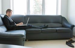 Affärsman Working med bärbara datorn på soffan Royaltyfri Fotografi