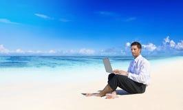 Affärsman Working på stranden royaltyfri foto