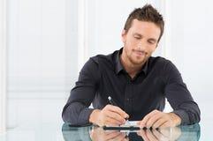 Affärsman Writing Document royaltyfri bild
