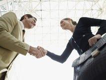 AffärsmanAnd Businesswoman Shaking händer mot tak royaltyfri bild