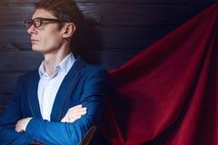 Affärsmananseende i en dräkt och röd kappa som superhero arkivfoton