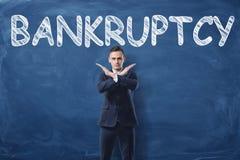 Affärsmananseende med hans händer som arg ` för tecken- och ord`-konkurs som är skriftlig på svart tavla bak honom royaltyfria foton