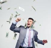 Affärsmananseende under pengarregn fotografering för bildbyråer