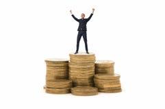 Affärsmananseendet på bunt av mynt med hans händer upp i att fira, poserar Royaltyfri Foto