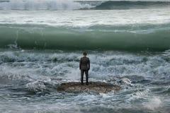 Affärsmananseendet vaggar på i havet som vänder mot annalkande vågor Royaltyfria Foton