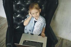 affärsmanbärbar dator genom att använda barn roliga exponeringsglas för barn Modestående av den lilla stiliga pojken i regeringss Royaltyfri Bild