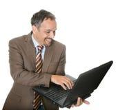 affärsmanbärbar dator som ler genom att använda royaltyfria foton