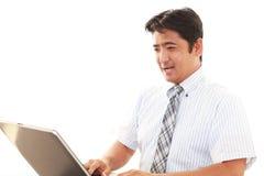 affärsmanbärbar dator som ler genom att använda arkivfoton