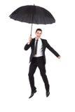 Affärsmanbanhoppning med ett paraply Royaltyfri Bild