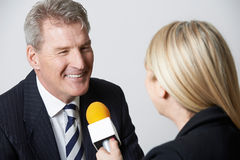 AffärsmanBeing Interviewed By kvinnlig journalist With Micropho fotografering för bildbyråer
