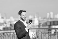 Affärsmanbrukssmartphone med leende Lycklig man med mobiltelefonen på solig terrass Stor ekonominyheter Kommunikation fotografering för bildbyråer