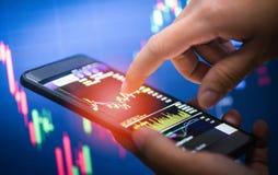 Affärsmanbrukssmartphone som handlar den online-skärmen för forex- eller för börsmarknad brädedata som är mobil i hand arkivfoto