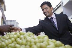 AffärsmanBuying Grapes In marknad arkivfoto