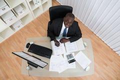 AffärsmanCalculating Bills In kontor Royaltyfria Foton