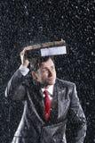 AffärsmanCovering Head With limbindning i regn royaltyfria foton